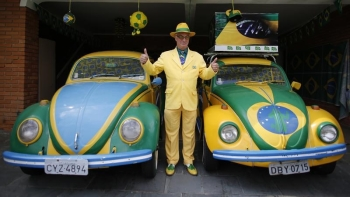 Brazilian attorney, Nelson Paviotti, poses with his two Volkswagen Beetles painted with the colors of the national flag in Campinas