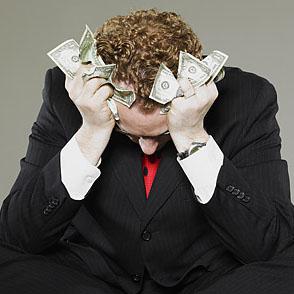 Mature businessman holding scrunched money