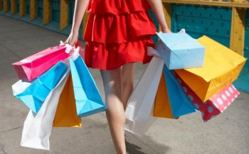 Young woman walking with shopping bags, low section