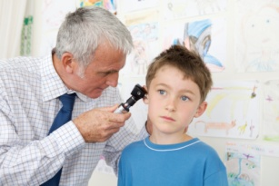 Doctor examining a boy's ear